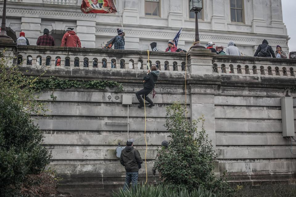 Trump supporters use ropes and barricades to scale a wall outside the US Capitol, January 06, 2021.