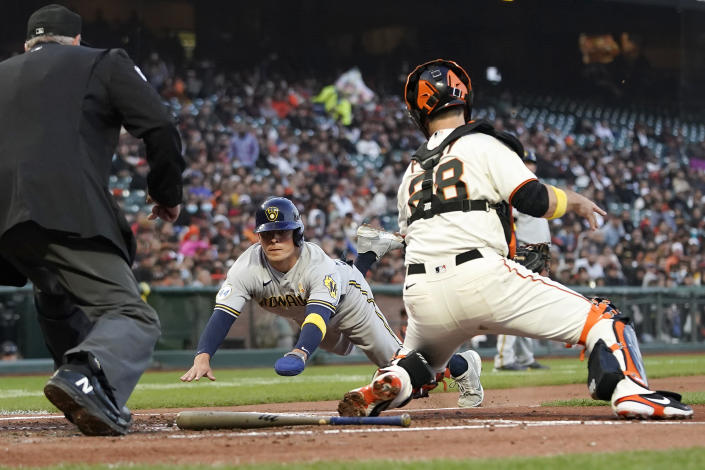 San Francisco Giants catcher Buster Posey, right, prepares to tag out Milwaukee Brewers' Luis Urias at home during the second inning of a baseball game in San Francisco, Wednesday, Sept. 1, 2021. (AP Photo/Jeff Chiu)