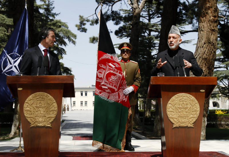 Afghan President Hamid Karzai, right, speaks during a joint press conference with the NATO Secretary-General Anders Fogh Rasmussen at the presidential palace in Kabul, Afghanistan, Thursday, April 12, 2012. President Hamid Karzai said he is considering calling presidential elections a year early to lessen the strain on Afghanistan that could be caused by the departure of foreign combat troops at the same time as a national ballot. (AP Photo/Rahmat Gul)