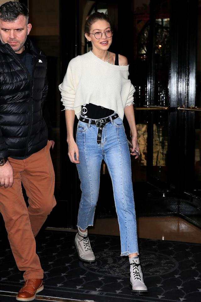 <p>In a ripped cropped Unravel Project knit sweater, black tank top, high-waisted belted jeans, white Doc Marten boots and rounded sunglasses leaving her hotel in Paris.</p>