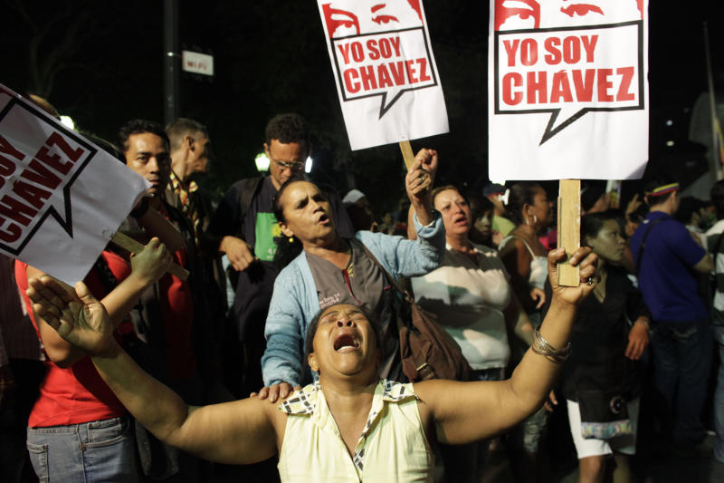 """A supporter of Venezuela's President Hugo Chavez cries as she holds a sign that reads in Spanish """"I am Chavez"""" as Chavistas gather in Bolivar square to mourn Chavez's death in Caracas, Venezuela, Tuesday, March 5, 2013. Venezuela's Vice President Nicolas Maduro announced that Chavez died on Tuesday at age 58 after a nearly two-year bout with cancer. During more than 14 years in office, Chavez routinely challenged the status quo at home and internationally. He polarized Venezuelans with his confrontational and domineering style, yet was also a masterful communicator and strategist who tapped into Venezuelan nationalism to win broad support, particularly among the poor. (AP Photo/Ariana Cubillos)"""