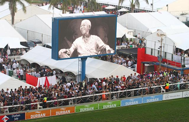 DURBAN, SOUTH AFRICA - JULY 06: A giant screen projects images of former president Nelson Mandela during the 2013 Vodacom Durban July at Greyville Racecourse on July 06, 2013 in Durban, South Africa. The main race of the day, the President's Champions Challenge, was won for the first time by a black jockey; S'manga Khumalo riding Heavy Metal. As a tribute to former president Nelson Mandela, who remains critically ill in hospital, sixty seven seconds of silence were observed. (Photo by Anesh Debiky/Gallo Images/Getty Images)