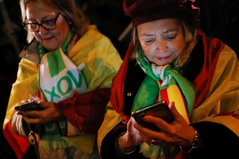 Supporters of Spain's far-right party VOX use their mobile phones to follow results in Spain's general election in Madrid