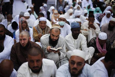 A Muslim pilgrim reads the Koran as he attends Friday prayers at the Grand mosque in the holy city of Mecca ahead of the annual haj pilgrimage in this October 11, 2013 file photo. REUTERS/Ibraheem Abu Mustafa/Files
