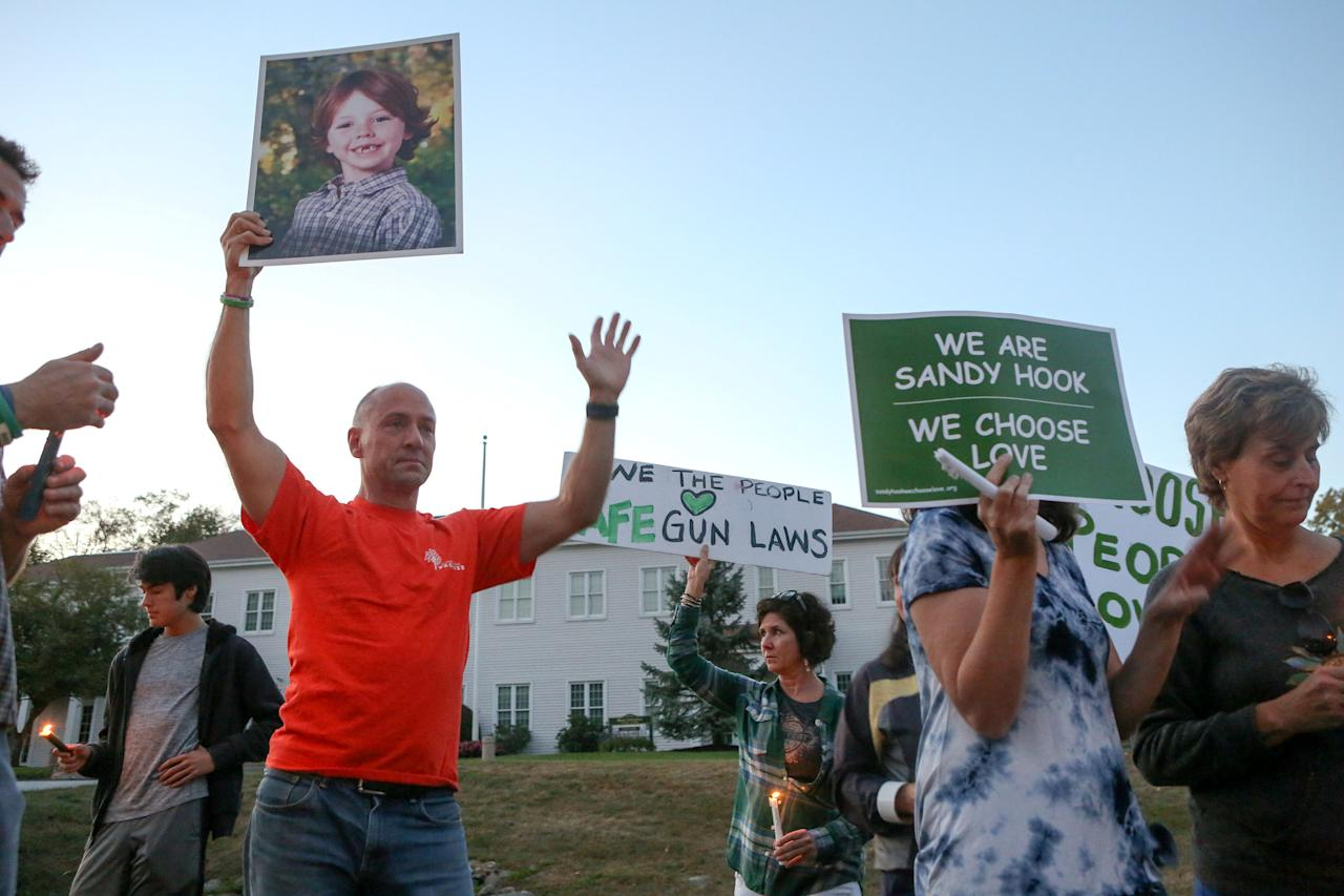 FILE PHOTO: Mark Barden, father of Sandy Hook school shooting victim Daniel, holds a photo of his son during a solidarity vigil in memory of victims of Las Vegas' Route 91 Harvest music festival mass killing, in Newtown, Connecticut U.S., the site of the 2012 Sandy Hook school shooting, October 4, 2017. REUTERS/Michelle McLoughlin/File Photo