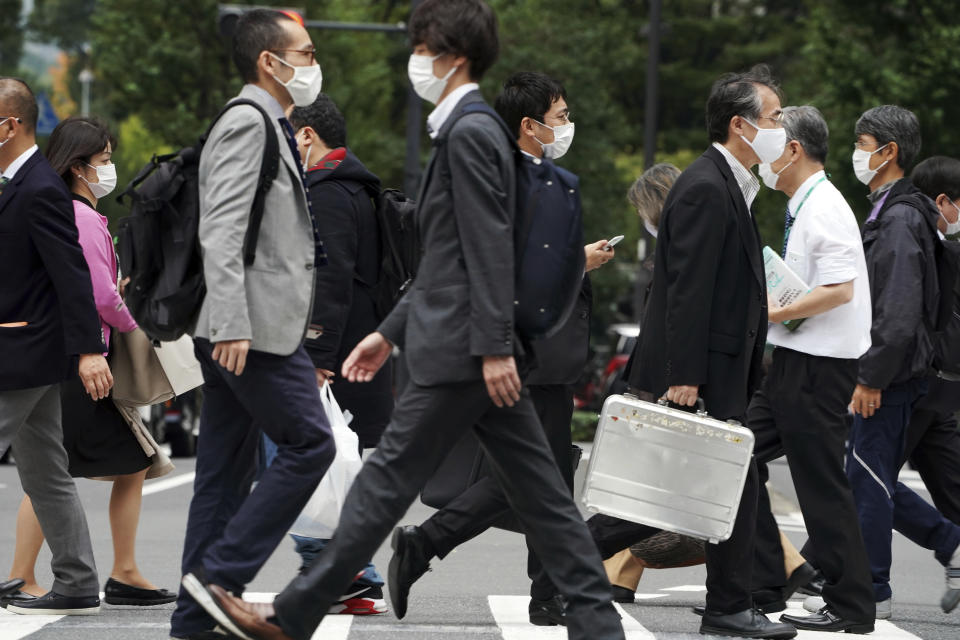 People wearing protective masks to help curb the spread of the coronavirus walk Monday, Nov. 2, 2020, in Tokyo. The Japanese capital confirmed more than 80 new coronavirus cases on Monday. (AP Photo/Eugene Hoshiko)