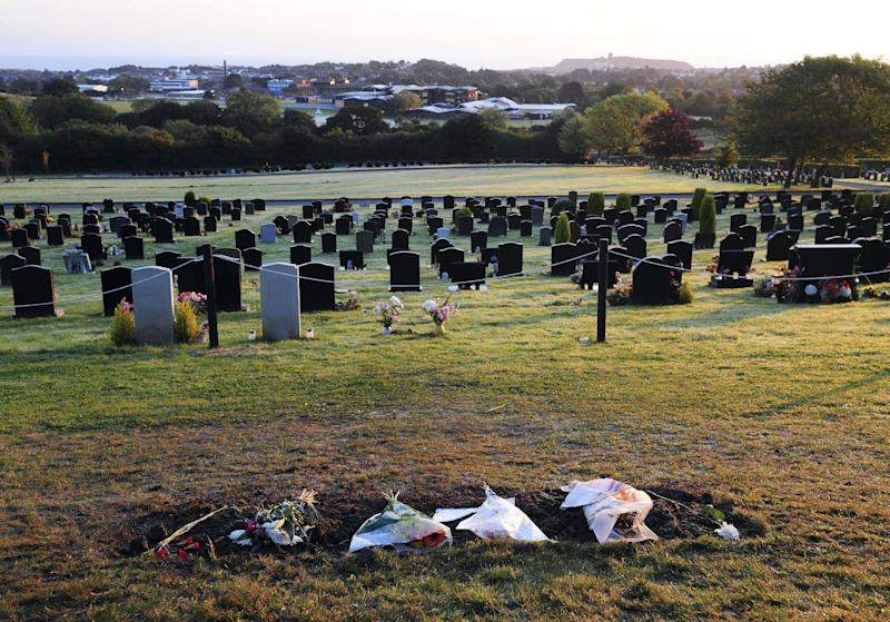 "A general view showing flowers left on the grave of  British TV host and Disc Jockey Jimmy Savile in Woodlands Cemetery, Scarborough, England, after the headstone was removed overnight at the request of Savile's family, Wednesday Oct. 10, 2012.  The family of Jimmy Savile have had the  headstone of from his grave removed  out of ''respect to public opinion"" after police said the former presenter could haveabused up to 25 victims over 40 years. (AP Photo/Anna Gowthorpe/PA)  UNITED KINGDOM OUT  NO SALES  NO ARCHIVE"