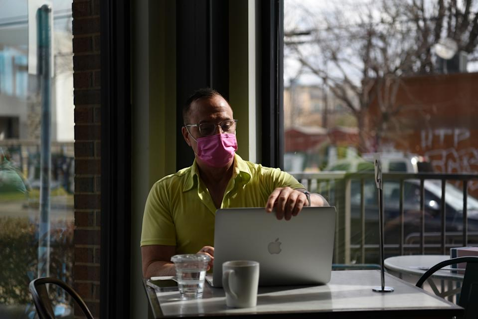 A man wearing a mask works on his laptop as the state of Texas prepares to lift its mask mandate and reopen businesses to full capacity during the coronavirus disease (COVID-19) pandemic in Houston, Texas, U.S., March 9, 2021. REUTERS/Callaghan O'Hare