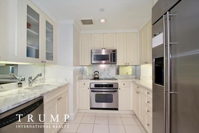The kitchen has white marble counters and floors.