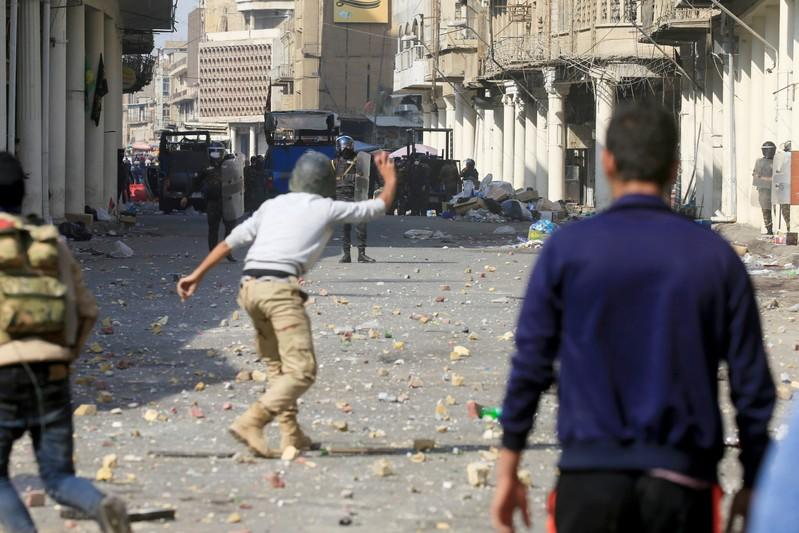 A demonstrator throws an object towards riot police during the ongoing anti-government protests in Baghdad