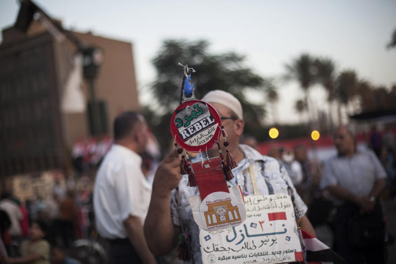 """FILE - In this file photo taken Wednesday, June 26, 2013, an Egyptian man holds a banner with an Arabic word Tamarod, or """"Rebel,"""" a campaign calling for the ouster of Egyptian President Mohammed Morsi and for early presidential elections, during a demonstration in Tahrir Square in Cairo, Egypt. No matter what happens in anti-Morsi protest planned for June 30, 2013, organizers of the petition campaign that led to it say they have created a grassroots network of new activists they hope will remain a voice for the public. (AP Photo/Manu Brabo, File)"""