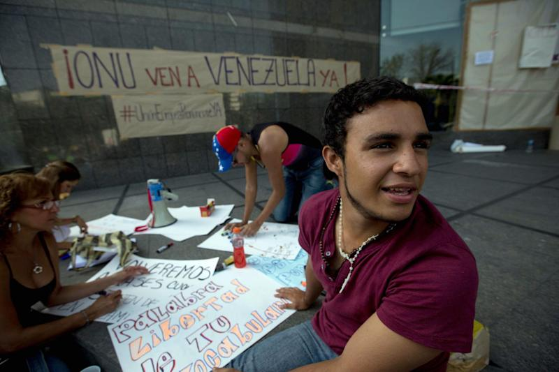 """Students make posters outside of United Nations office in Caracas, Venezuela, Tuesday, March 25, 2014. The large banner on the building reads in Spanish """"UN come to Venezuela now"""". The large group of protesting anti-government students have camped in front of the office of the United Nations asking it to come and observe the situation, as Venezuela's bloody political standoff heads into its third month. The decision to pitch tents on the concrete sidewalk along one of Caracas' busiest, smog-filled streets comes as foreign ministers from several South American nations arrive Tuesday to lend support to President Nicolas Maduro's efforts at reconciliation with his opponents. (AP Photo/Fernando Llano)"""