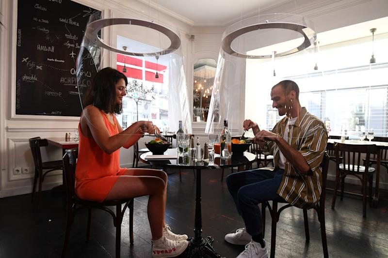 TOPSHOT - A couple has a lunch under plexiglass protection designed by Christophe Gernigon at the H.A.N.D restaurant, on May 27, 2020 in Paris, as France eases lockdown measures taken to curb the spread of the COVID-19 pandemic, caused by the novel coronavirus. (Photo by ALAIN JOCARD / AFP) (Photo by ALAIN JOCARD/AFP via Getty Images)