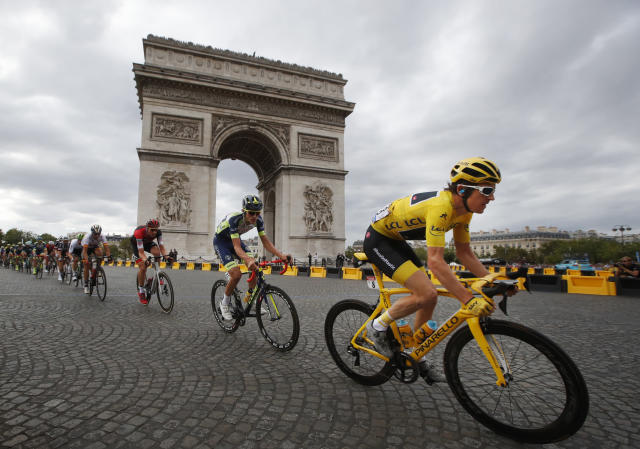 Tour de France winner Geraint Thomas, of Britain, wearing the overall leader's yellow jersey, passes the Arc de Triomphe on July 29, 2018, during the twenty-first stage of the 116-kilometer (72.1-mile) Tour de France cycling race from Houilles to the Champs-Elysees in Paris. (AP Photo/Christophe Ena)
