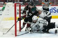 Arizona Coyotes left wing Michael Bunting (58) pushes the puck further into the net on a goal by Jakob Chychrun as Los Angeles Kings defensemen Drew Doughty (8) and Kings Mikey Anderson (44) defend in vain during the first period of an NHL hockey game Wednesday, May 5, 2021, in Glendale, Ariz. (AP Photo/Ross D. Franklin)