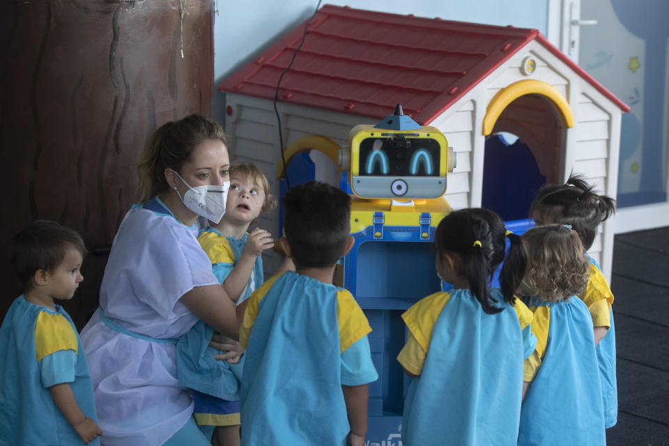 A teacher demonstrates a robot that takes the temperature of children and displays it on a screen in a kindergarten in Madrid, Spain, Friday, Sept. 4, 2020. Spain has become the first western Europe to accumulate more than 1 million confirmed infections as the country of 47 million inhabitants struggles to contain a resurgence of the coronavirus. (AP Photo/Paul White)