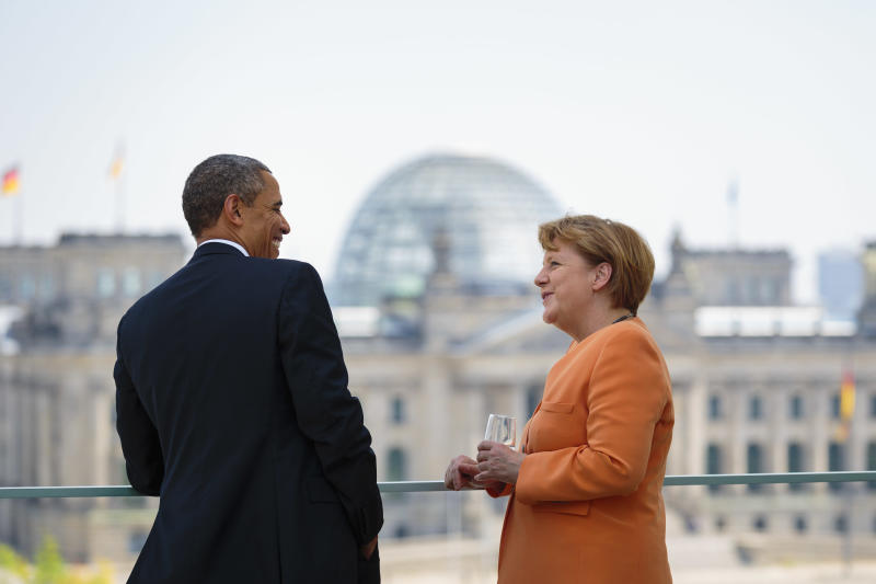 In this picture publicly provided by the German Government's Press Office, German chancellor Angela Merkel, right, shares a smile with US President Barack Obama at the chancellery in Berlin, Wednesday June 19, 2013. In background the German Parliament building, the Reichstag. On the second day of his visit to Germany, Obama met with German President Joachim Gauck and Chancellor Angela Merkel before delivering a speech at Brandenburg Gate. (AP Photo/Steffen Kugler, Bundesregierung)