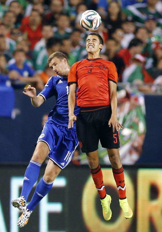 Mexico's Reyes and Bosnia and Herzegovina's Dzeko jump for the ball during their international friendly soccer match in Chicago