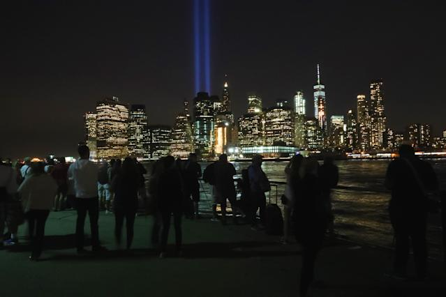 <p>People take photos of the Tribute in Light from Brooklyn Bridge Park on Sept. 11, 2017. (Gordon Donovan/Yahoo News) </p>