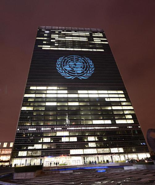 The UN logo is projected onto the United Nations headquarters in New York on November 22, 2013 (AFP Photo/Emmanuel Dunand)