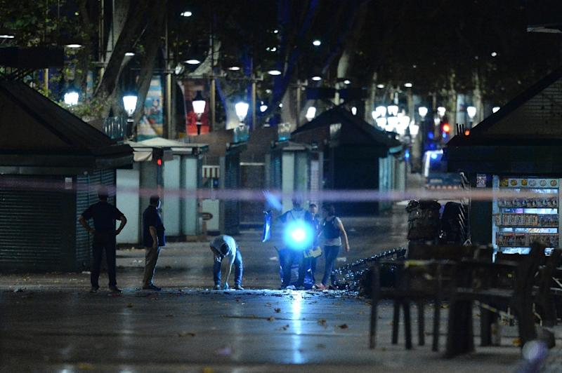 Policemen check the streets after towing away the van which ploughed into a crowd, killing at least 13 people and injuring around 100 others on Las Ramblas in Barcelona (AFP Photo/Josep LAGO)