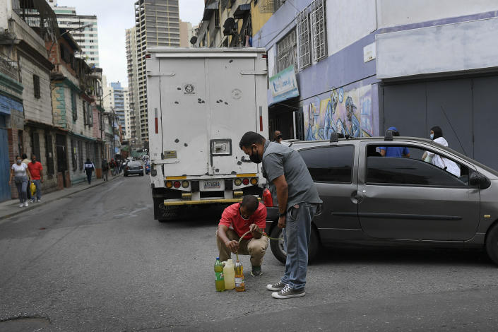 Men siphon from a car gasoline that they will store and then return to the gas station to fill up again, in the San Juan neighborhood of Caracas, Venezuela, Tuesday, Jan. 19, 2021, amid the new coronavirus pandemic. Filling stations will only fill up car and motorcycle tanks, but not containers to avoid people from storing gasoline. Venezuela's economic crisis has sent millions fleeing and those left behind lacking basic goods, including gasoline, in a country with one of the world's largest proven oil reserves. (AP Photo/Matias Delacroix)
