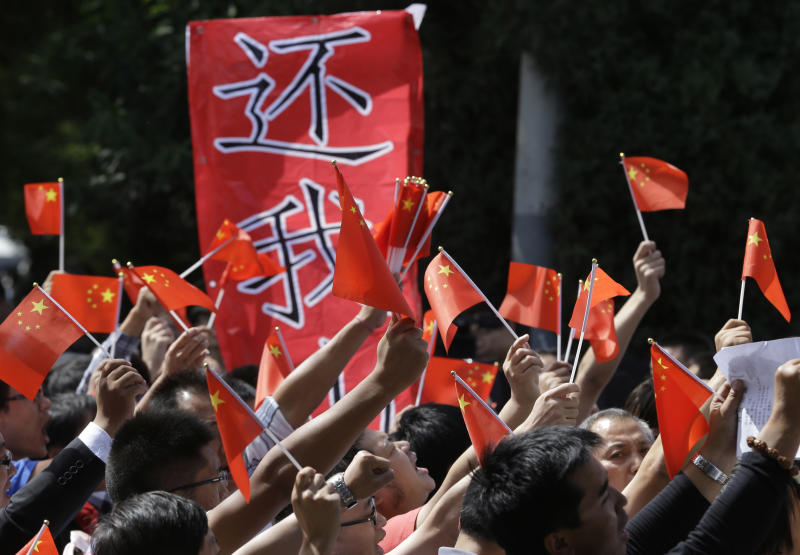 """Chinese protesters march with a banner which reads """"Return My Mountains"""" outside the Japanese embassy in Beijing, China, Wednesday, Sept. 12, 2012. A territorial flare-up between China and Japan intensified as two Beijing-sent patrol ships arrived near disputed East China Sea islands in a show of anger over Tokyo's purchase of the largely barren outcroppings from their private owners. (AP Photo/Ng Han Guan)"""