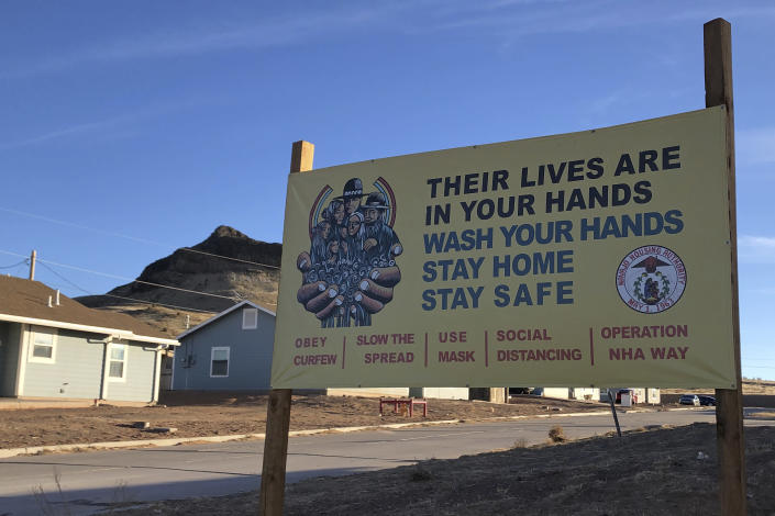 A sign urging safety measures during the coronavirus pandemic is seen in Teesto, Arizona, on the Navajo Nation on Feb. 11, 2021. Teesto workers, health representatives, volunteers and neighbors keep close tabs on another to ensure the most vulnerable citizens get the help they need. (AP Photo/Felicia Fonseca)