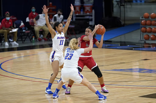 St. John's guard Leilani Correa, right, looks to pass the ball as DePaul guards Sonya Morris, left, and Dee Bekelja defend during the first half of an NCAA college basketball game in Chicago, Wednesday, Jan. 13, 2021. (AP Photo/Nam Y. Huh)
