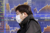 A man walks by an electronic stock board of a securities firm in Tokyo, Wednesday, Jan. 20, 2021. Asian shares were mostly higher Wednesday, ahead of Joe Biden's inauguration as president, ending President Donald Trump's four-year term. Japan's benchmark lost early gains as worries grew about the surge in coronavirus cases. (AP Photo/Koji Sasahara)