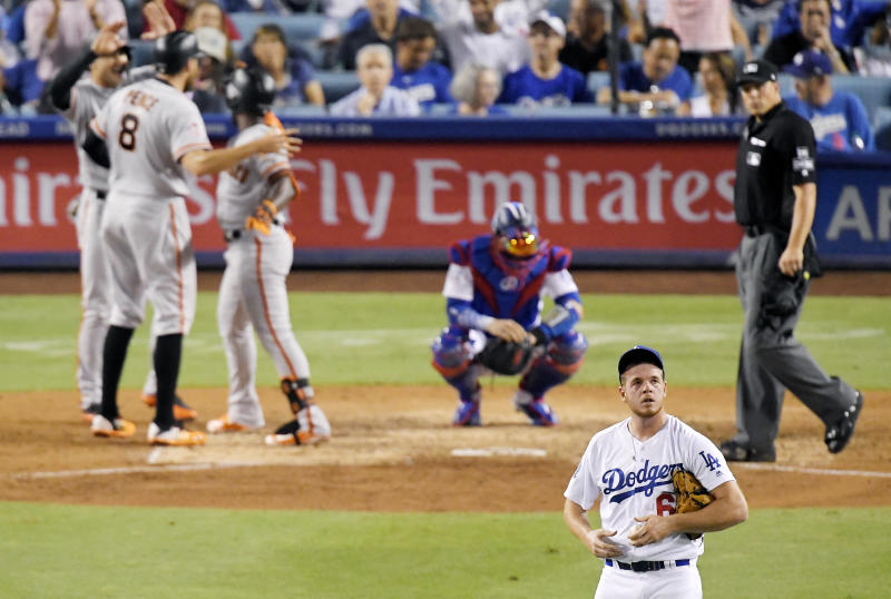 San Francisco Giants' Andrew McCutchen, third from right, celebrates with Chase d'Arnaud, left, and Hunter Pence after hitting a three-run home run off Los Angeles Dodgers starting pitcher Caleb Ferguson, foreground, during the eighth inning of a baseball game Wednesday, Aug. 15, 2018, in Los Angeles. (AP Photo/Mark J. Terrill)