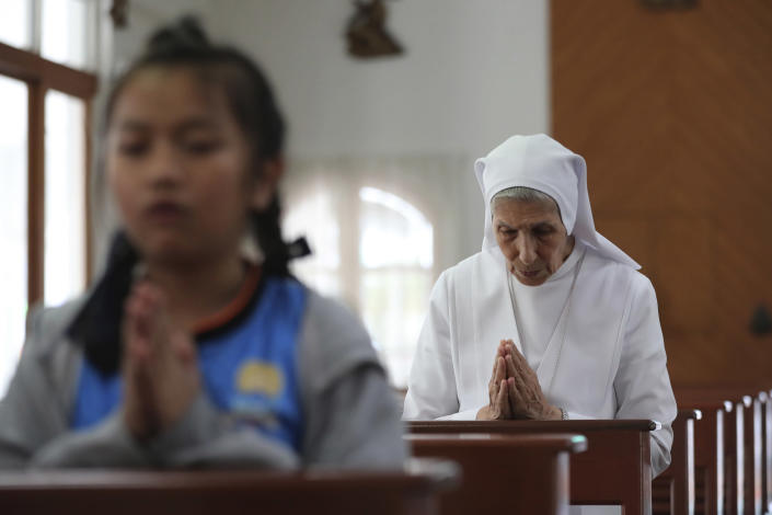 In this Aug. 27, 2019, photo, ST. Mary's School Vice Principal Sister Ana Rosa Sivori, right, prays with students inside a church at the girls' school in Udon Thani, about 570 kilometers (355 miles) northeast of Bangkok, Thailand. Sister Ana Rosa Sivori, originally from Buenos Aires in Argentina, shares a great-grandfather with Jorge Mario Bergoglio, who, six years ago, became Pope Francis. So, she and the pontiff are second cousins. (AP Photo/Sakchai Lalit)