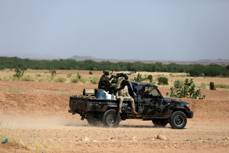 FILE PHOTO: Nigerian army soldiers board a pickup to escort Nigerians heading north towards Libya as they leave Agadez