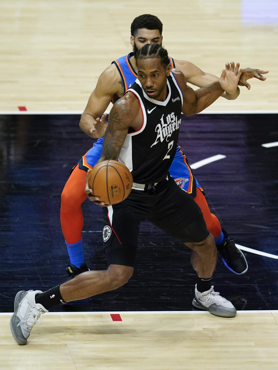 Los Angeles Clippers forward Kawhi Leonard (2) controls the ball against Oklahoma City Thunder guard Kenrich Williams (34) during the first quarter of an NBA basketball game Sunday, Jan. 24, 2021, in Los Angeles. (AP Photo/Ashley Landis)