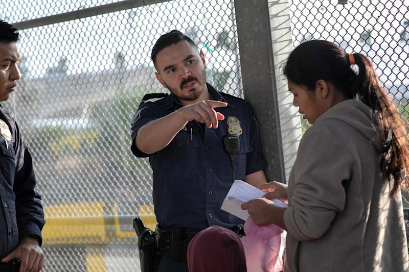 A U.S. Customs and Border Protection officer instructs an asylum seeker to wait in line on the international bridge from Mexico to the United States on December 09, 2019 next to the border town of Matamoros, Mexico. (Photo: John Moore/Getty Images)