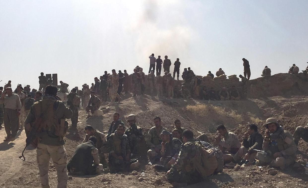 Peshmerga soldiers wait and watch behind fortified position while exlosion goes off down the road. (Photo: Ash Gallagher for Yahoo News)