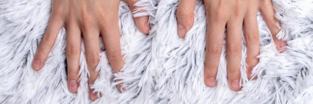 Pair of hands on a soft furry blanket.
