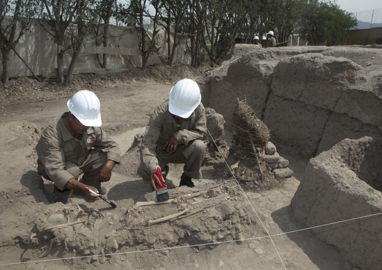 Archaeologists brush the bones of a skeleton, for the benefit of the media, during excavations to unearth ancient tombs discovered in the sports complex where Peru's national soccer team practices in Lima, Peru, Tuesday, Feb. 26, 2013. According to Peru's Ministry of Culture, 11 pre-Inca tombs belonging to the Lima culture (200-700 AD) and Yschma (1100-1400 AD) were located inside the sports complex in the district of San Luis, where excavations started in Dec. 2012. (AP Photo/Martin Mejia)