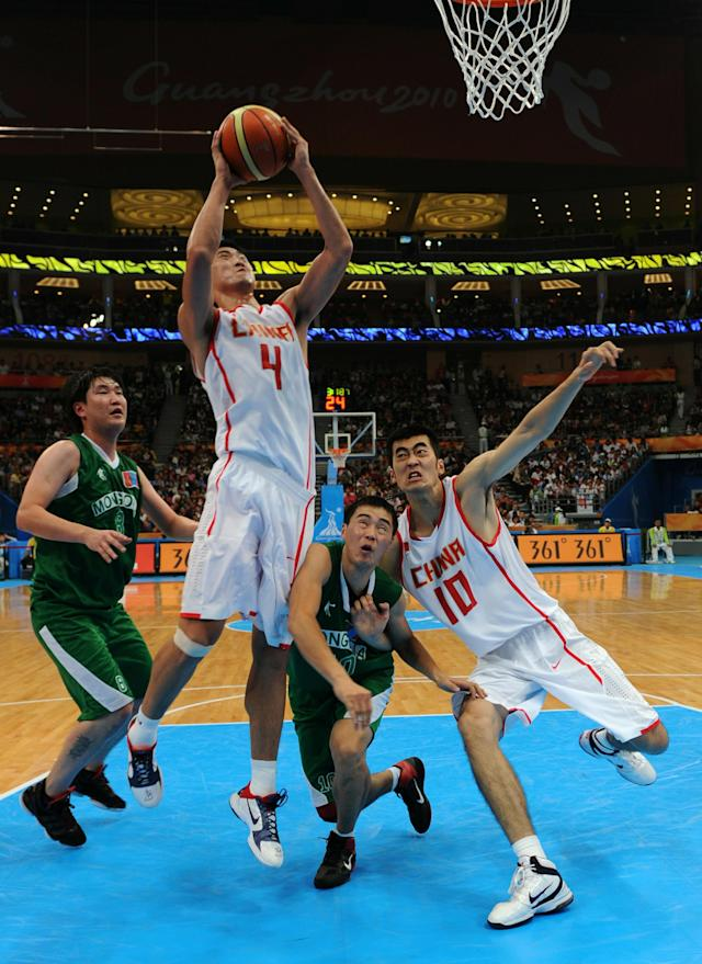 Ding Jinhui of China (2nd L) attempts a basket with help from compatriot Zhang Zhaoxu (R) as Uuganbayar Oyuntsetseg of Mongolia (2nd R) and compatriot Sainbayar Oyunbileg attempt to stop the ball during the men's preliminary round group E basketball match at the Guangzhou International Sport Arena during the 16th Asian Games on November 16, 2010. China won 91:46. AFP PHOTO / Antony DICKSON (Photo credit should read ANTONY DICKSON/AFP/Getty Images)