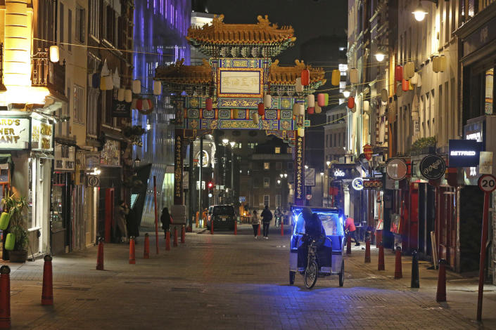 A quiet Wardour Street in London, as the New Year's Eve fireworks display has been cancelled due to the coronavirus pandemic, Thursday, Dec. 31, 2020. (Jonathan Brady/PA via AP)