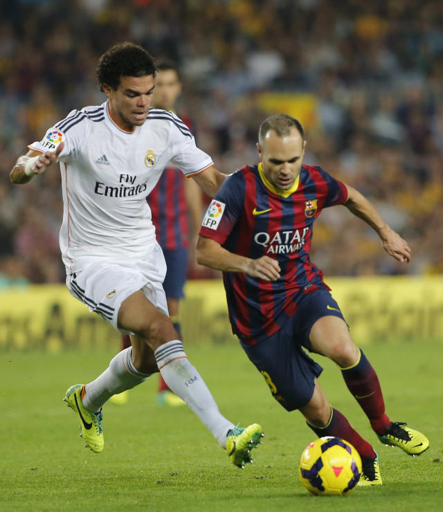 Barcelona's Andres Iniesta, right, in action with Real Madrid's Pepe, left, during a Spanish La Liga soccer match between Barcelona F.C. and Real Madrid at the Camp Nou stadium in Barcelona, Spain, Saturday, Oct. 26, 2013. (AP Photo/Emilio Morenatti)