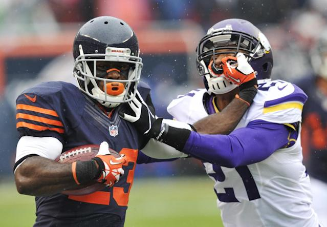 Chicago Bears' Devin Hester (23) pushes off Minnesota Vikings' Josh Robinson (21) while running a kickoff return during the first half of an NFL football game on Sunday, Sept. 15, 2013, in Chicago. (AP Photo/Jim Prisching)