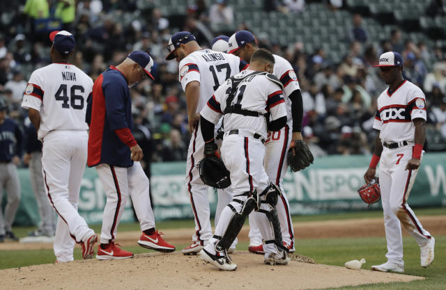 Chicago White Sox manager Rick Renteria, second from left, talks with his team as he waits for relief pitcher Ryan Burr during the third inning of a baseball game against the Seattle Mariners in Chicago, Sunday, April 7, 2019. (AP Photo/Nam Y. Huh)