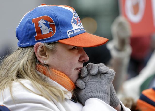 Denver Broncos fan Nancy Scollon tries to keep warm as she waits for the Broncos players to arrive at their team hotel Sunday, Jan. 26, 2014, in Jersey City, N.J. The Broncos are scheduled to play the Seattle Seahawks in the NFL Super Bowl XLVIII football game Sunday, Feb. 2, in East Rutherford, N.J. (AP Photo/Mark Humphrey)