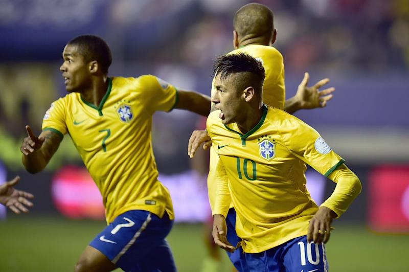 Brazil players Neymar (R) and Douglas Costa (L) celebrate after scoring against Peru during their 2015 Copa America football match, in Temuco, Chile, on June 14, 2015