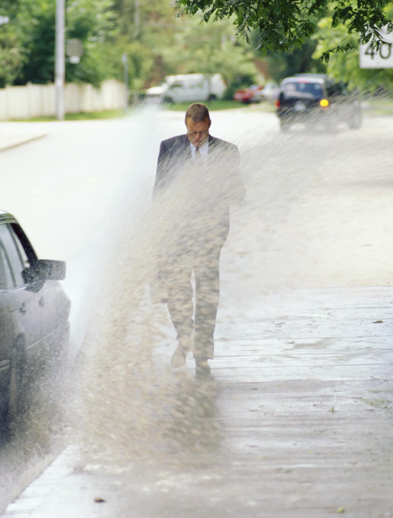A man being splashed with mud by a passing car – an offence if you're in NSW and also splashing someone at a bus stop.