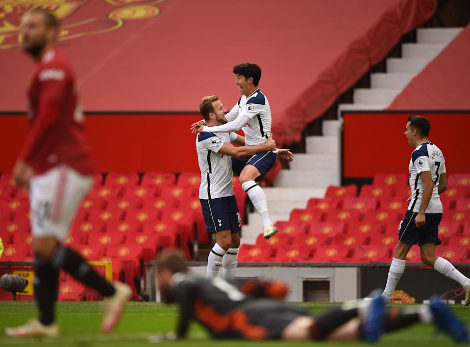 Tottenham Hotspur's South Korean striker Son Heung-Min (C) jumps into the arms of Tottenham Hotspur's English striker Harry Kane (C left) after he scored their second goal during the English Premier League football match between Manchester United and Tottenham Hotspur at Old Trafford in Manchester, north west England, on October 4, 2020. (Photo by Oli SCARFF / AFP) / RESTRICTED TO EDITORIAL USE. No use with unauthorized audio, video, data, fixture lists, club/league logos or 'live' services. Online in-match use limited to 120 images. An additional 40 images may be used in extra time. No video emulation. Social media in-match use limited to 120 images. An additional 40 images may be used in extra time. No use in betting publications, games or single club/league/player publications. /  (Photo by OLI SCARFF/AFP via Getty Images)