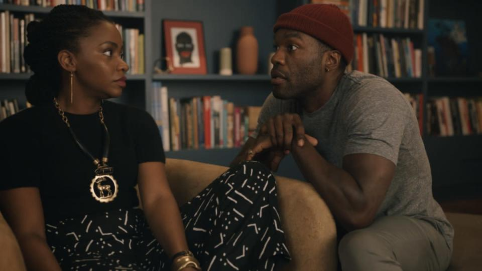 Yahya Abdul-Mateen II and Teyonah Parris sit together on a couch in Candyman film