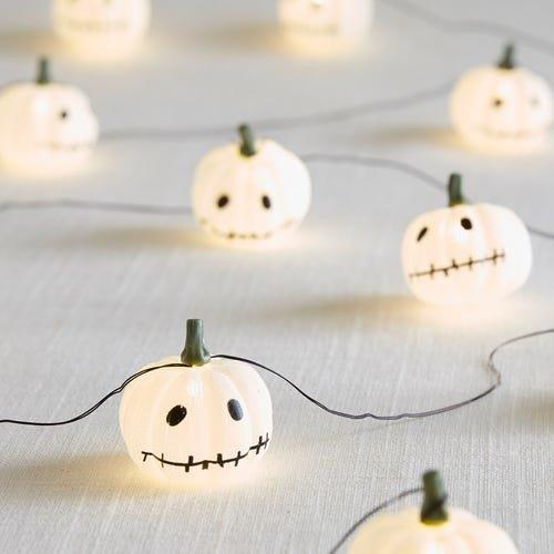 """<p>Just on the tasteful side of spooky, this 10-foot-long string of white mini pumpkins with stitched-up smiles works with any Halloween decorating scheme. Weave them through the centerpiece on your table, hang them above an entryway, or wrap them around a mirror for an eerie little twinkle.</p> <p><b>To buy: </b>Stitched Pumpkin LED Glimmer String, $20, <a href=""""http://www.anrdoezrs.net/links/7876406/type/dlg/sid/RS%2CAffordableHalloweenPartyDecorationsThatWon%2527tScareYourWallet%2Ckholdefehr1271%2CHOL%2CIMA%2C679877%2C201910%2CI/https://www.pier1.com/stitched-pumpkin-10-led-glimmer-strings/4114601.html?"""" target=""""_blank"""">pier1.com</a>. </p>"""