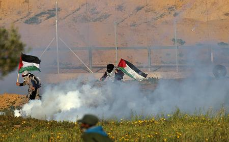 Women holding Palestinian flags run away from tear gas fired by Israeli forces during a protest at the Israel-Gaza border fence, in the southern Gaza Strip